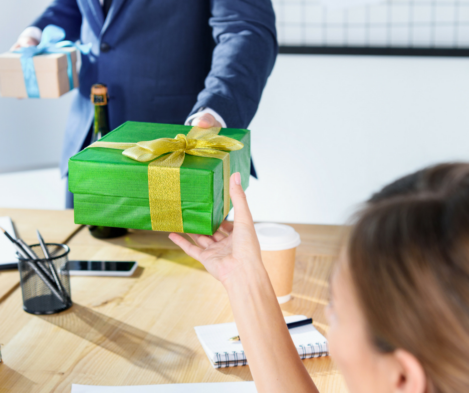 coworker handing a gift & Co-Worker Gift Ideas for Anyone on Your List This Year