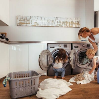 A woman is doing laundry along wth two children.